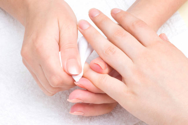 manicure applying - wiping the mosturizer from cuticles
