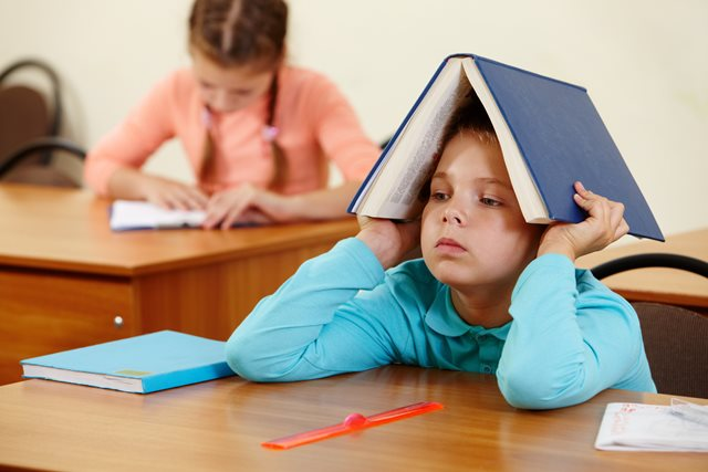 Cute schoolboy keeping open book on head in classroom